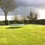 large garden with trampoline and hedge